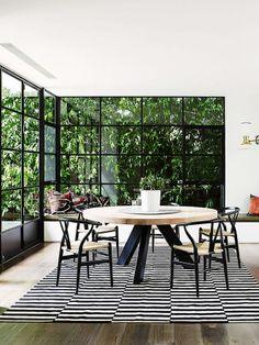 Mesa de Jantar Redonda. Black steel windows. Timber table with black steel legs