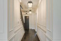 Chic foyer features floor to ceiling wainscoted walls illuminated by a row of carriage lanterns leading to a black front door.