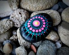 Painted Spiral on natural Pebbles -The Eco nature way for art  My painted rocks and pebbles are full of happiness and joy, they love to travel around the world and spread colors to every home they arrives.  This painted Spiral is made on natural pebble stone with colorfull desigh with acrilic. After I paint the pebbles I apply varnish cover. this pebble stone decor is made with a lot of love to nature. It has mandala desighn on it with the colors of pink, Turquoise, yellow, pink and orange…