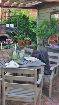 slate sideboard.. wooden chairs, great table, lots of greenery.. love the pergola