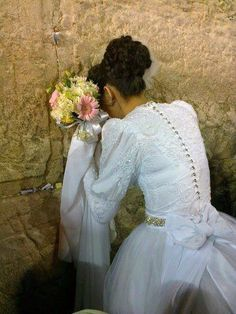 A Jewish bride praying at the Western Wall. aww so sweet God bless her :)
