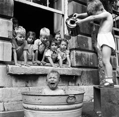 Little girl being showered with a watering can as she sits in a tub of water. This scene, was taken at Ashley Road Day nursery, Bristol. August 1953.