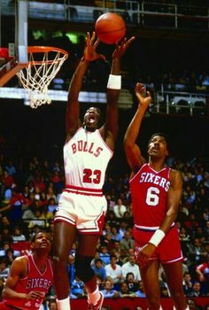 The GOAT explodes upwards between Maurice Cheeks and Dr. J in Chicago.