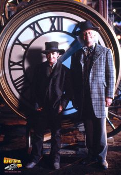 Michael J. Fox and Christopher Lloyd pose in front of the series' famous clock.