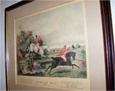 Framed Equestrian Lithograph Print entitled, Bachelors Hall, Plate 2. We estimate this Lithograph is from the early 1900s. This Wood Framed Print measures 20 Horizontal x 18.5 Vertical. It has a beige Mat. Notice the Red Frock Coats and Black Top Hats worn by the Riders out for a hunt that day. There is a Rider on a beautiful white horse jumping a fence, another in front of him rides an exceptional black stallion as he waves his top hat at another Rider across the field. Bachelors Hall…