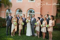 Bridesmaids in mis-matched blush and champagne cocktail dresses, and groomsmen in grey suits