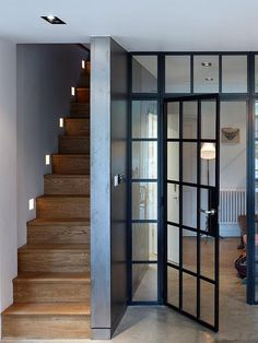 escalier : Internal steel-framed windows and doors act as a transparent screen between the living and eating spaces in the basement. A set of wood stairs with modern detailing leads up to the ground floor. The Doors, Windows And Doors, Black Windows, Sash Windows, Crittal Doors, Crittall Windows, Steel Frame Doors, Wood Doors, Stair Lighting