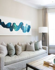 Neutral pillows with a few soft green accents are a subtle call out to this eye-catching wall art in this contemporary living room designed by Victoria Elizabeth Design