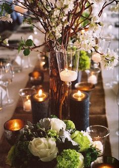 An elegant and autumnal centerpiece full of candles, a shimmery brown table runner, white flowers to attract light and pieces of wood to make it more rustic and vintage | Image via beehiveevents.com