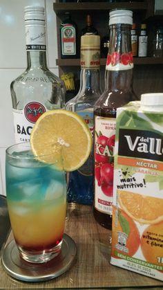 * BARBADOS SURPRISE * - 60 ml. Rum Carta Blanca - 15 ml. Licor Curaçau Blue - 60 ml. Suco de Laranja - 15 ml. Xarope de Grenadine - 01 rodela de Laranja (para decoração) - Misture o rum e o licor curaçau blue em um mixing glass e reserve. - Coloque o xarope de grenadine em um copo Collins e encha-o de gelo. - Com a ajuda de uma colher bailarina, coloque bem devagar, o suco de laranja pela borda do copo. - Repita o processo com a mistura de rum e licor curaçau blue. - Decore com uma rodela de…