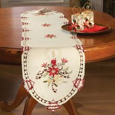 "Holiday Candles Table Runner By Collections Etc by Collections. $11.99. Embroidered poinsettias, candles, bells and pine cones; Measures 68""L x 13""W; Use over a tablecloth or on its own; Embroidered ecru table runner features detailed cut work; Add heirloom elegance to your holiday table. Add some heirloom charm to your holiday table with this embroidered ecru table runner. It s detailed cut work and embroidered poinsettias, holiday candles, bells and pine cones. Use ..."