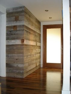 Entryway wall built with reclaimed barn wood. Concealed closet door.