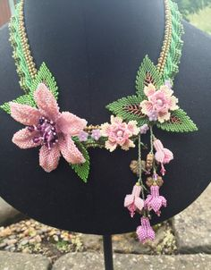 This stunning hand beaded necklace, will make you stand out in the crowd. A herringbone collar embellished with pretty hand beaded flowers and leaves and finished with crystals, fresh water pearls and flower and leaf beads. The pinks and purples make this a beautiful and feminine statement piece, ideal for parties and weddings.
