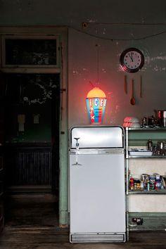 Slurpee lighting on a vintage fridge with open restaurant shelving. Very cool.  Bloodandchampagne.com