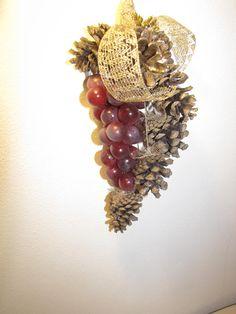 ciao a tutti questo decoro natalizio è stato realizzato con pigne naturali,nastro dorato e frutta artificiale