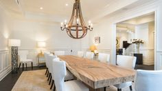 The more formal dining room has a natural wood slab table with contemporary high-backed chairs in white. The large iron chandelier hanging above adds to the rustic charm invoked by the table.  By Meridith Baer Home.