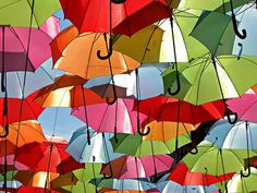 Agueda, Protugal - A beautiful colorful umbrellas installation in the town of Agueda in Portugal. A complete street was decorated with umbrellas suspended and floating in the air, all captured in images by photographer Patricia Almeida. Umbrella Art, Under My Umbrella, Umbrella Street, Portugal, Instalation Art, Colorful Umbrellas, Parasols, Fantastic Art, Awesome