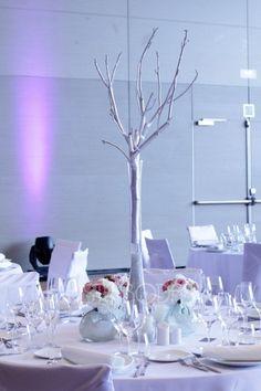 Detalle de decoraci�n para una boda con centro de mesa alto y detalles en blanco y plata.