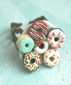 This ring features a plate of handmade Christmas inspired donuts made from polymer clay. The mini donuts sit on a ceramic plate that measures about an inch in diameter. The plate is securely attached Christmas Donuts, Merry Christmas To All, Handmade Christmas, Christmas Crafts, Polymer Clay Miniatures, Polymer Clay Charms, Polymer Clay Jewelry, Mini Donuts, Doughnuts