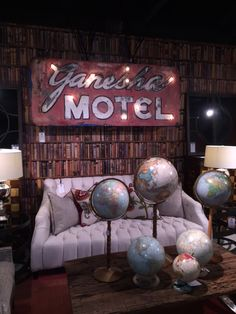 Shown is our Library-Multi wallpaper, Rochester Sofa and vintage Ganesha Motel sign. #andrewmartin #interiordesign #decor #furniture #sofa #tufted #wallpaper #library #vintage #signs #globes