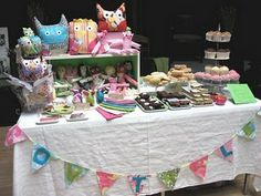 Different heights, using shelf and tiered cake holder brings visual interest. Colour theme plus bunting at the front.