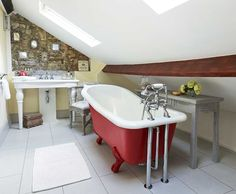stone cottage bathroom with red roll top bath