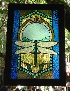 Stained glass blue dragonfly and lotus panel with walnut wood frame and brass hangers.