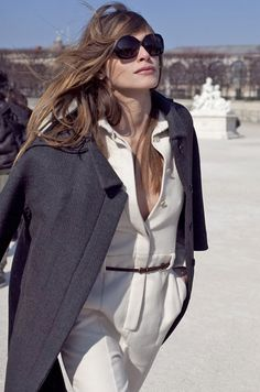 white ensemble, dark belt for contrast, interesting style jacket, jackie o sunglasses, and wind-blown hair