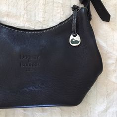 """Authentic Dooney and Bourke Black Leather Hobo Bag Gorgeous and classic leather bag!  This is a total steal!  Like new condition, clean and stain free throughout.  The only flaw is a small hole on the zipper.  The zipper is still functional, just treat with care.  Other than that, this bag looks brand new!  10"""" X 15"""" X 6"""" Dooney & Bourke Bags"""