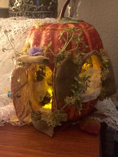 One of my favorite,hand decorated fairy houses.this being a hollowed out styrofoam fall pumpkin,with seed pod,lace,bead,& silk flower embellishments and a batt.op. T-lite in the roof
