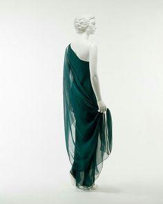 Vihreä iltapuku, silkkiä. Kreikkalaistyylinen, toinen olkapää paljaana, keveyttä, kerroksellisuutta. 1970 luku, Halston USA. Metmuseum.