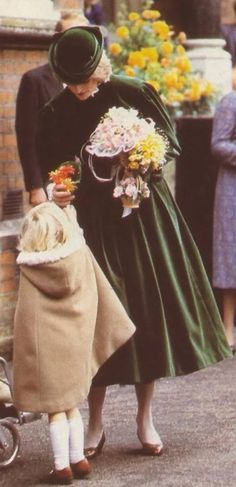 November 2, 1982:  Princess Diana accepts flowers from a child at the Royal School for the Blind in Leatherhead, Surrey, during the opening of a new extension to the school.