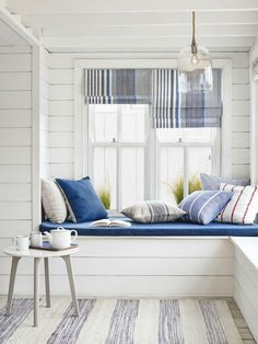 There's a real coastal feel to this New England style room. Whites mixed with slubby linens, stripes, and a blue, white and grey palette give an updated sunny nautical feel to the room.