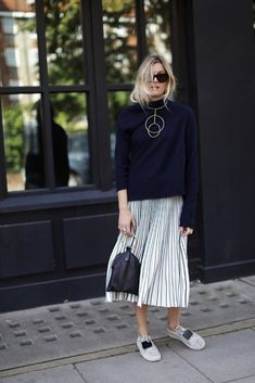 Blogger Camille Over the Rainbow wears a sweater, statement necklace, pleated midi skirt, sneakers, and a top-handle clutch