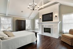 Here we have another example of high vaulted ceiling over master bedroom featuring marble hearth with TV mounted above, dark hardwood flooring and white details all around.