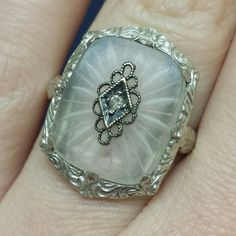 Gorgeous 14K white gold Camphor/Rock Crystal ring featuring a beautiful, rectangular cut Camphor/Rock Crystal that measures approximately 16x13mm. It has a small Diamond set in the center. The ring dates between the 1910-1920's.