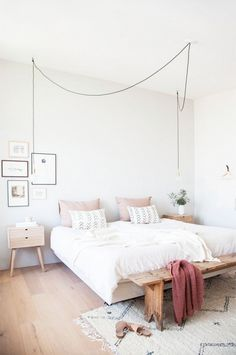 Feminine bedroom with a low platform bed, a stringed pendant light, and a reclaimed wood bench