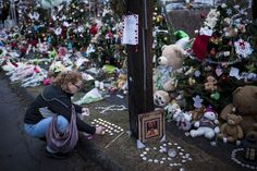 A woman lights candles at a makeshift memorial near the entrance to the grounds of Sandy Hook Elementary School on Dec. 18, in Newtown, Conn.