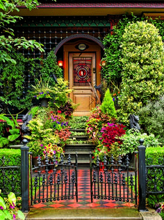 Pots of richly hued coleus and geraniums line the front steps, accenting both stained glass and paint colors, while a passion vine clambers over the Saracenic arch.