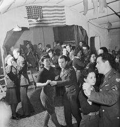 British Land Army girls and members of the Women's Royal Air Force (WAAF) dance with men of the US Eighth Army Air Force in Suffolk during 1943.