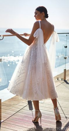 Unique and romantic short tea length wedding dress with open back | Vintage a-line bridal dress with glamorous bow detail on the strap | Ida Torez Wedding Dresses 2021 Brave Glanze Collection - 01223 - Tempting Mouth | How to Choose a Wedding Dress in 2021- Belle The Magazine | See more gorgeous bridal gowns by clicking on the photo