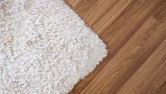 Close-up white carpet on laminate wood floor in living room, interior decoration Installing Hardwood Floors, Wood Laminate Flooring, How To Wash Rugs, White Shag Rug, White Carpet, Rug Store, Pet Home, Craft Organization, Cleaning Solutions