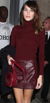 Alexa Chung in a leather skirt and slim turtleneck from Versus, a round tote and lasercut flats.