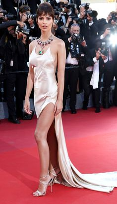 EMILY RATAJKOWSKI : After modeling her layers of Bulgari necklaces completely naked, the model hits the red carpet in a pink satin custom Twinset slip gown with a thigh-high slit, plus strappy sandals and faux bangs.