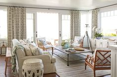 A wood-paneled ceiling is low-key and casual, and slide doors don't need any room to swing (they're amazing space savers!). If your home gets a lot of sunlight, choose fadeproof fabric for your curtains. Similar glass bottles, birchlane.com. Tray, $129 for two, birchlane.com. Coffee table and sofa, restorationhardware.com. Rug, westelm.com. Sofa pillow fabric, fschumacher.com. Drapery fabric, kravet.com. - HouseBeautiful.com