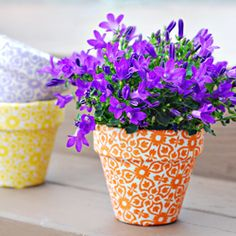 Add some style to your patio garden by decorating  your terracotta pots with some colorful fabric!