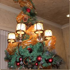 Greenery, ornaments and copper deco mesh make for a festive chandelier