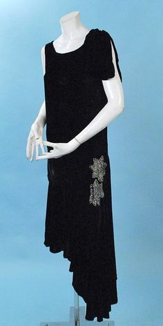 1920s Elegant black silk velvet flapper gown with sparkling French paste rhinestone trim in flower shapes on one hip. Little velvet petal shaped detail on one shoulder dropped waist with nice fit at hips, uneven hem, bias cut skirting, no closures, cream colored silk liner in skirt only. Front sideway