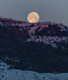 The moon sets behind a mountain shining with alpenglow