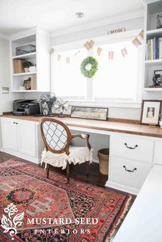 wall to wall desk built on top of cabinets.  bookshelves on top flanking windows